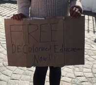 "A UCT student holds a sign calling for ""free decolonised education now"". She was standing outside of Parliament, with other students, hoping to engage passers-by to further and deepen the debate on free education. PHOTO: Saarah Survé"