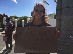 "A UCT student holds a sign which says ""Money for military. No funds for our future"". She was standing outside of Parliament hoping to engage passers-by to further and deepen the debate on free education. PHOTO: Saarah Survé"